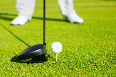 Golf Ball on Tee, Man about to Hit Ball with Driver photo