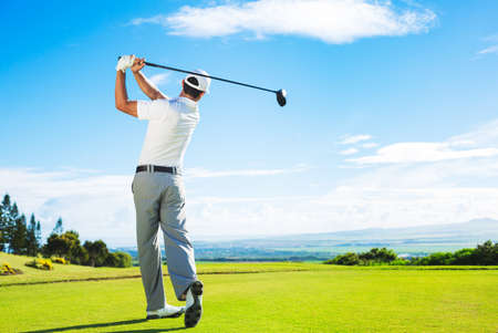 Man Playing Golf on Beautiful Sunny Green Golf Course Hitting Golf Ball down the Fairway from the Tee with Driver.