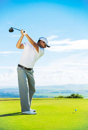 swings: Man Playing Golf on Beautiful Sunny Green Golf Course. Hitting Golf Ball down the Fairway from the Tee with Driver.