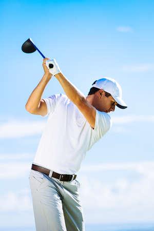 Man Swinging Golf Club with Blue Sky Background Standard-Bild