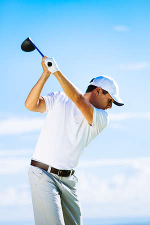 Man Swinging Golf Club with Blue Sky Background Stock Photo