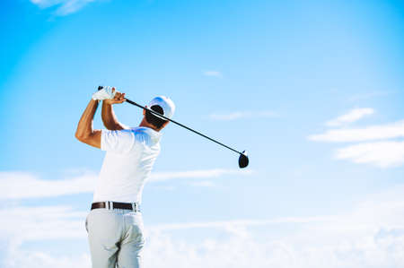 Man Swinging Golf Club with Blue Sky Background Foto de archivo
