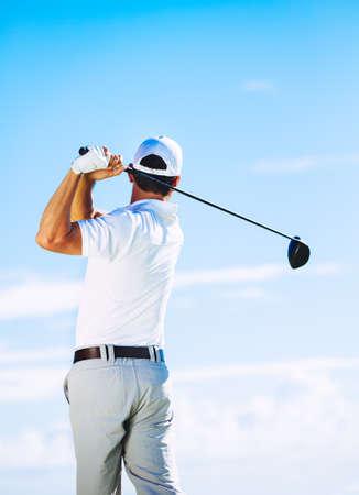 Man Swinging Golf Club with Blue Sky Background photo
