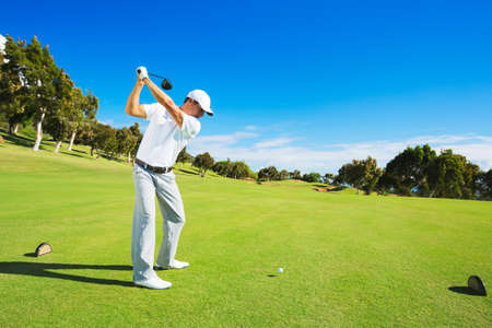 off: Golf player teeing off. Man hitting golf ball from tee box with driver. Stock Photo