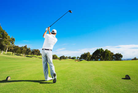 off course: Man hitting golf ball from tee box with driver. Stock Photo