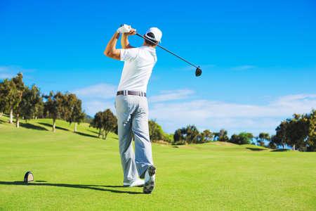 Man raakt golfbal uit tee box met chauffeur. Stockfoto