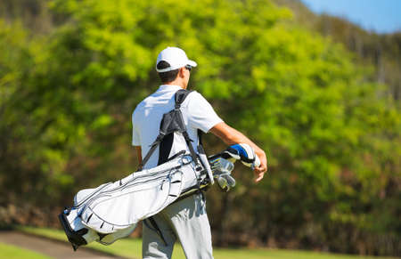 Golfer with Golf Bag Walking down the Course photo