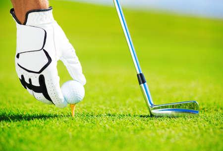 Tee에 골프 공을 두는 남자, 세부 사항을 닫습니다