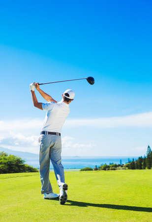 Golfista que golpea la bola con el club en el hermoso campo de golf