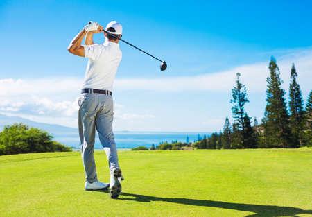 columpios: Golfista golpear la bola con el club en el hermoso campo de golf