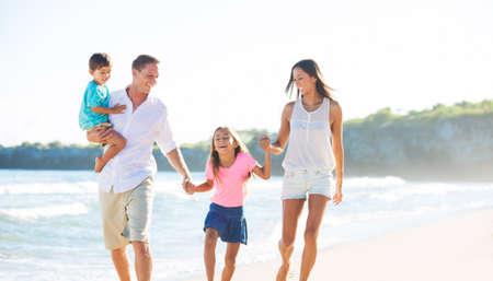 幸せな混血家族 4 人が浜辺で遊んで