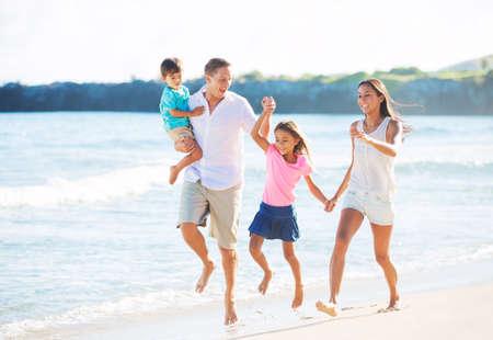 resor: Lycklig Mixed Race Familj av fyra leker på stranden