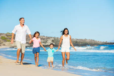 Happy Mixed Race Family of Four on the Beach photo