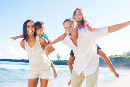 Happy Mixed Race Family of Four Playing on the Beach Banco de Imagens