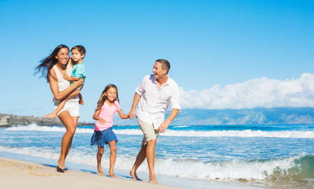 Happy Mixed Race Family of Four Playing on the Beach Archivio Fotografico