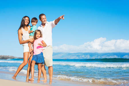 Happy Mixed Race Family of Four Playing on the Beach photo
