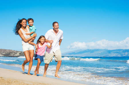 Lycklig Mixed Race Familj av fyra på stranden