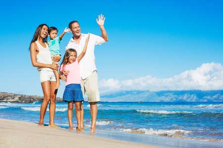 Feliz familia de raza mixta de cuatro juegan en la playa Foto de archivo