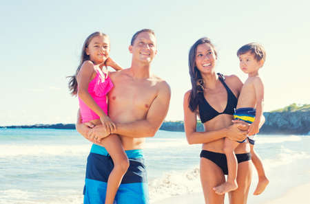Happy Mixed Race Family of Four on Sunny Beach. Tropical Beach Family Vacation. photo