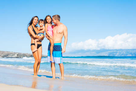 carrying girl: Happy Mixed Race Family of Four on Sunny Beach. Tropical Beach Vacation