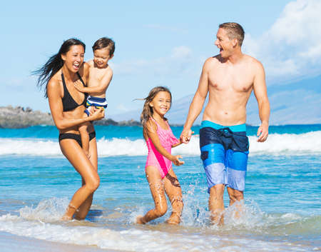 Happy Mixed Race Family of Four Playing and Having Fun on the Beach photo