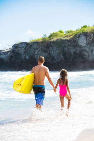 surf girl: Father and Daughter on the Beach going Surfing Together in Hawaii, Summer Lifestyle Family Concept