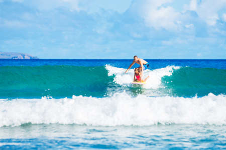 Father and Daughter Surfing Together Catching Wave, Summer Lifestyle Family Concept photo