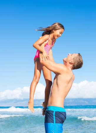 Father and Daughter Playing on Tropical Beach Vacation photo