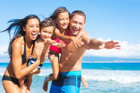 asian bikini: Happy Mixed Race Family of Four Playing and Having Fun on the Beach. Tropical Beach Family Vacation.