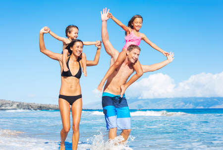 Happy Mixed Race Family of Four Playing and Having Fun on the Beach. Tropical Beach Family Vacation. photo