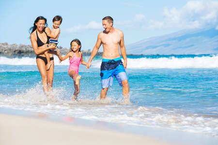 child in bikini: Happy Mixed Race Family of Four Playing and Having Fun on the Beach. Tropical Beach Family Vacation.