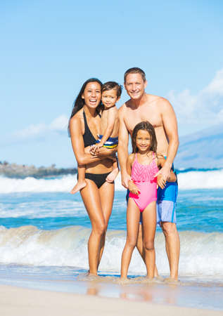 Happy Mixed Race Family of Four on Tropical Sunny Beach Standard-Bild