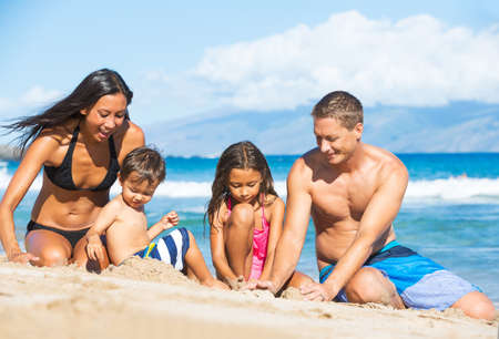 Happy Mixed Race Family of Four Playing and Having Fun on the Beach in the Sand. Tropical Beach Family Vacation. photo