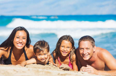 diverse family: Happy Mixed Race Family of Four Playing and Having Fun on the Beach in the Sand. Tropical Beach Family Vacation. Stock Photo
