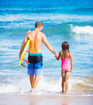 Father and Daughter on the Beach going Surfing Together in Hawaii, Summer Lifestyle Family Concept photo