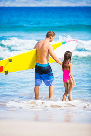 Father and Daughter on the Beach going Surfing Together in Hawaii photo