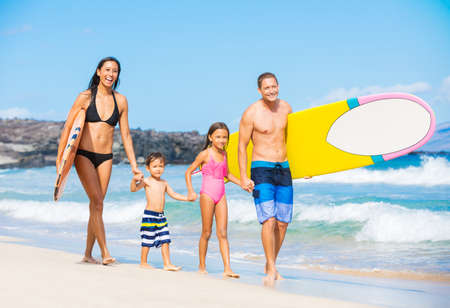 Happy Family with Surfboards on the Beach in Hawaii photo
