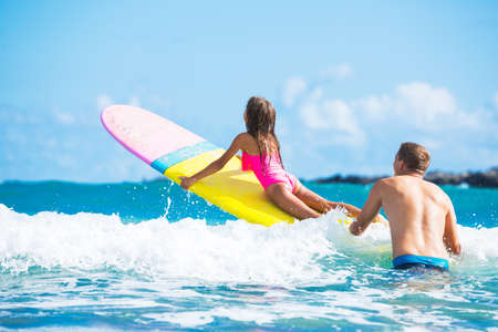 father daughter: Father and Daughter Surfing Together, Summer Lifestyle Family Concept Stock Photo
