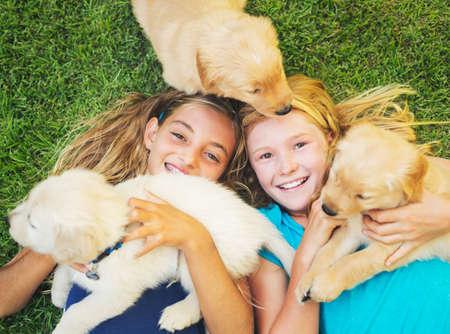 amigos abrazandose: Adorable lindo que juega chicas jóvenes y cachorros Abrazo