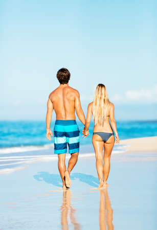 Happy Attractive Couple Walking on Beautiful Sunny Beach    photo
