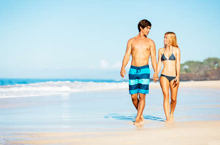 bikini couple: Happy Attractive Couple Walking on Beautiful Sunny Beach