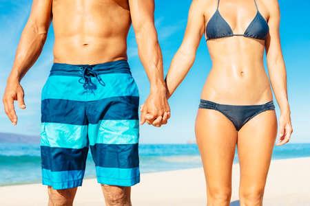 手を繋いでいる水着でビーチに魅力的なフィットのカップル