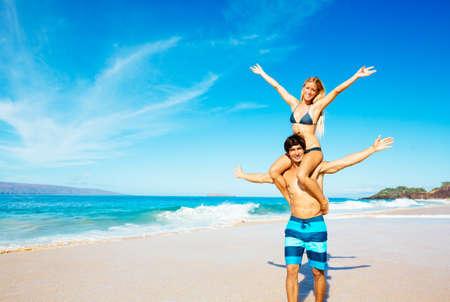 幸せな魅力的なカップルを再生し、美しい晴れたビーチで楽しんで