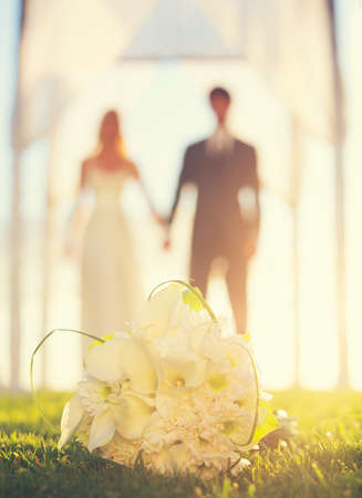 Close up of Wedding Bouquet. Focus on Flowers. Bride and Groom in Background. Stock Photo