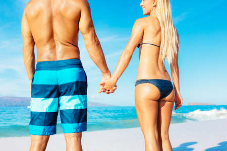 bikini couple: Attractive Fit Couple on the Beach in Swimwear Holding Hands