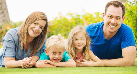 playing field: Portrait of Happy Family of Four Outside. Parents and Two Young Children Stock Photo