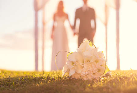 Close up of Wedding Bouquet. Focus on Flowers. Bride and Groom in Background. Stok Fotoğraf