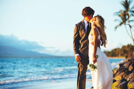 luna de miel: Romántica boda de los pares que se besan en la playa al atardecer