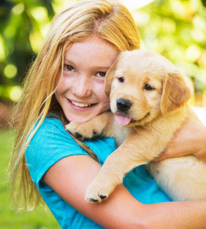 Adorable Cute Young Girl Playing and Hugging Puppies photo