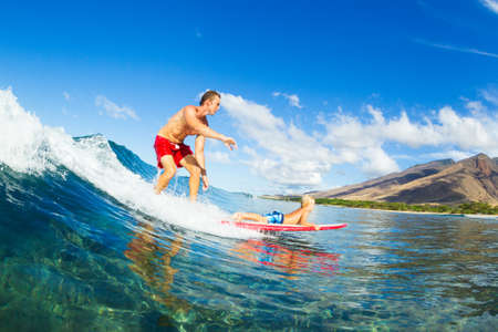 fatherhood: Father and Son Surfing Together. Riding Wave on Surfboard Tandem. Fatherhood, Family Fun Outdoor Lifestyle.